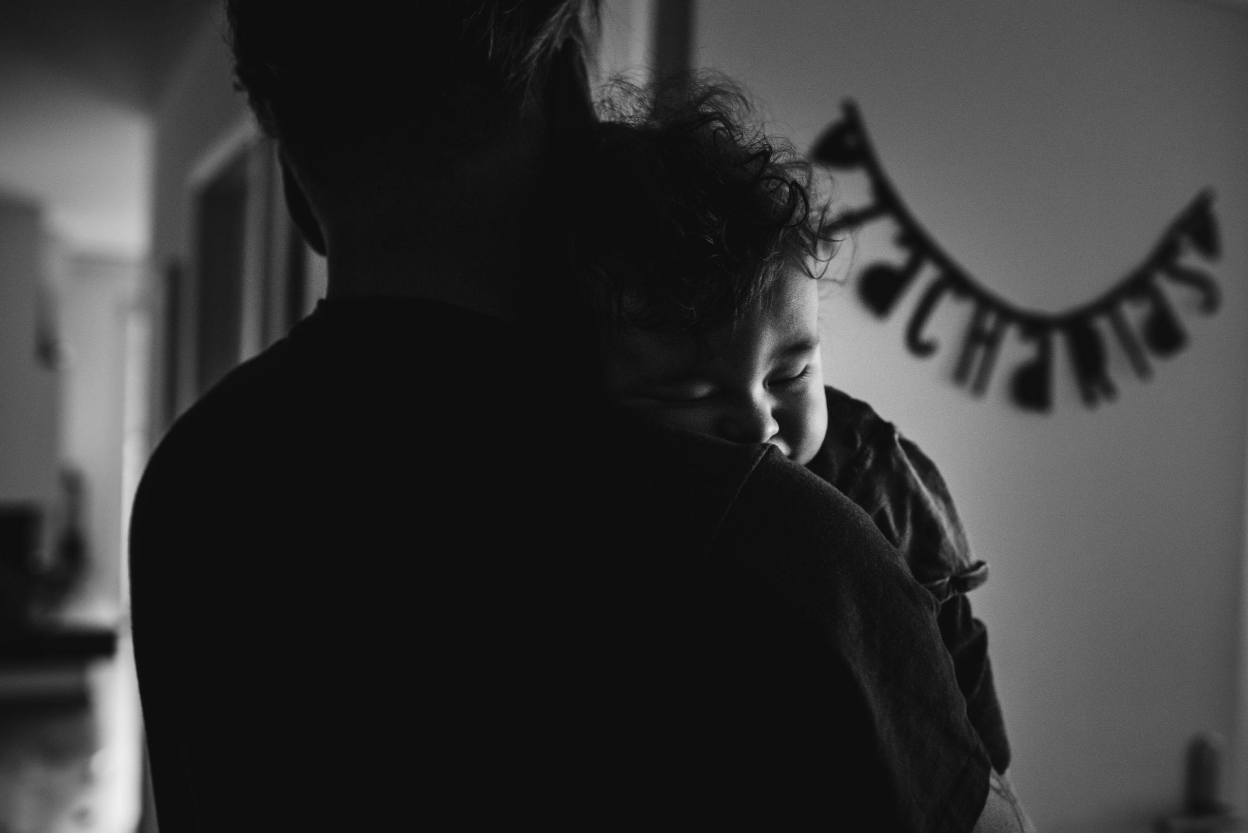 Kleinkind schläft in den Armen vom Vater
