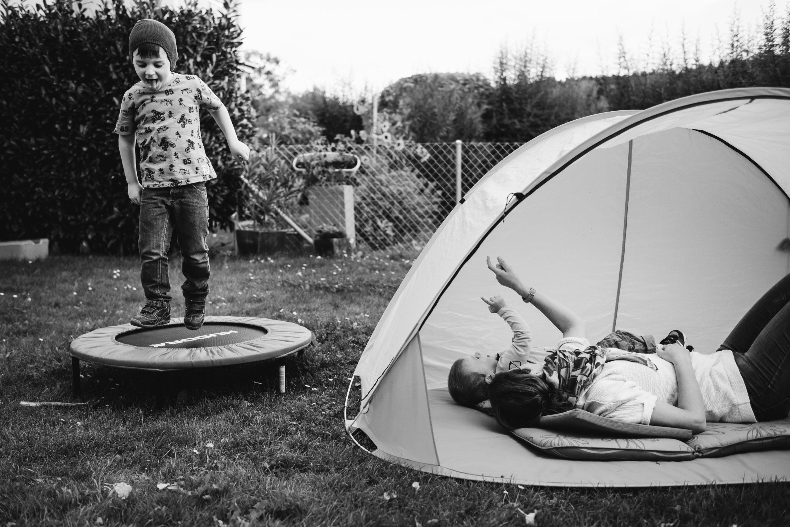 Kind hüpft auf Trampolin während Mutter und Bruder im Zelt im Garten sind
