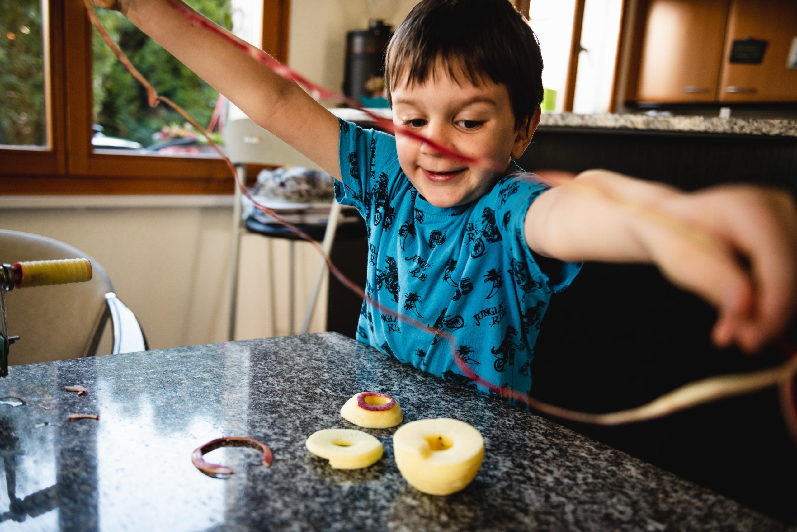 Kind lacht und hält lange Apfelschale in den Händen