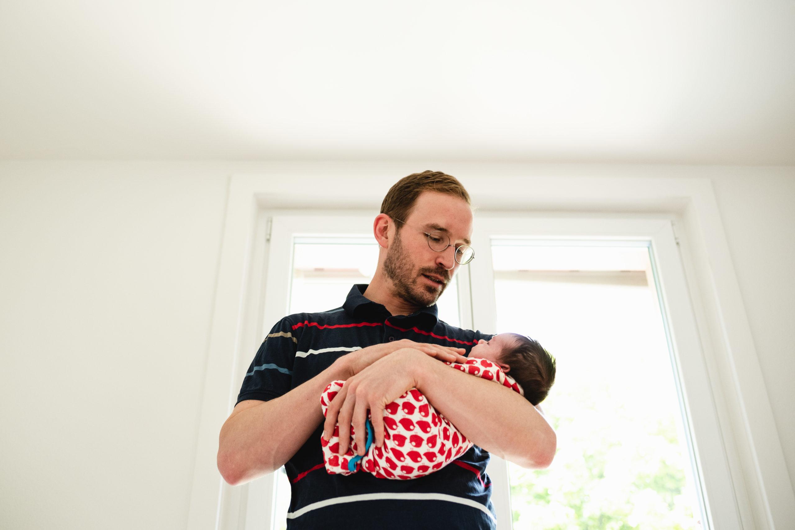 Vater hält in den Armen neugeborenes Baby vor einem Fenster