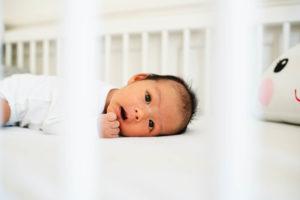 Neugeborenes Baby im Babybett schaut in dei Kamera durch die Stangen des Bettes