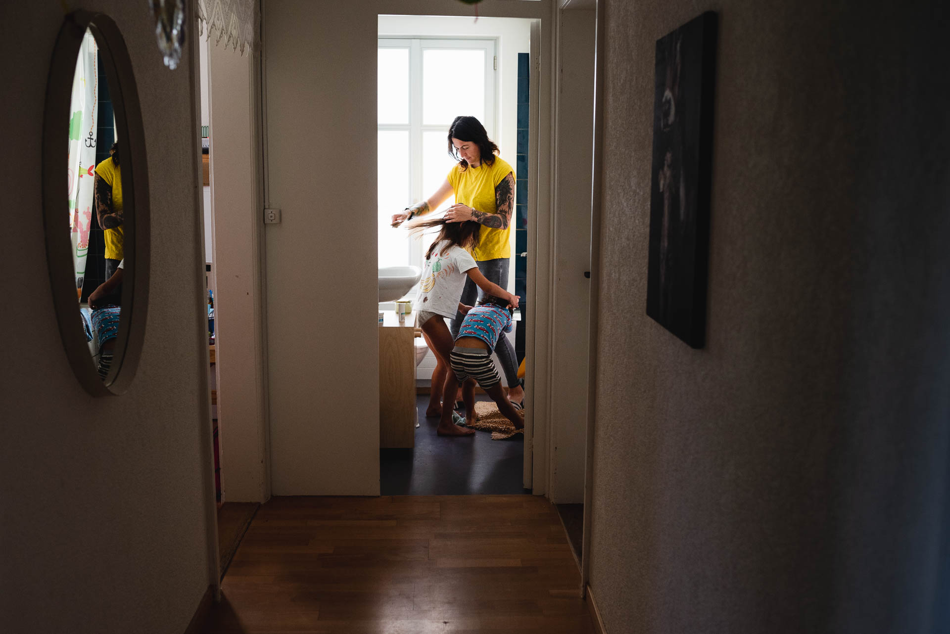 Ansicht durch das Korridor ins Badezimmer, wo eine Mutter die Haare der Tochter kämmt. Währenddessen der Sohn klemmt an ihren Beinen.