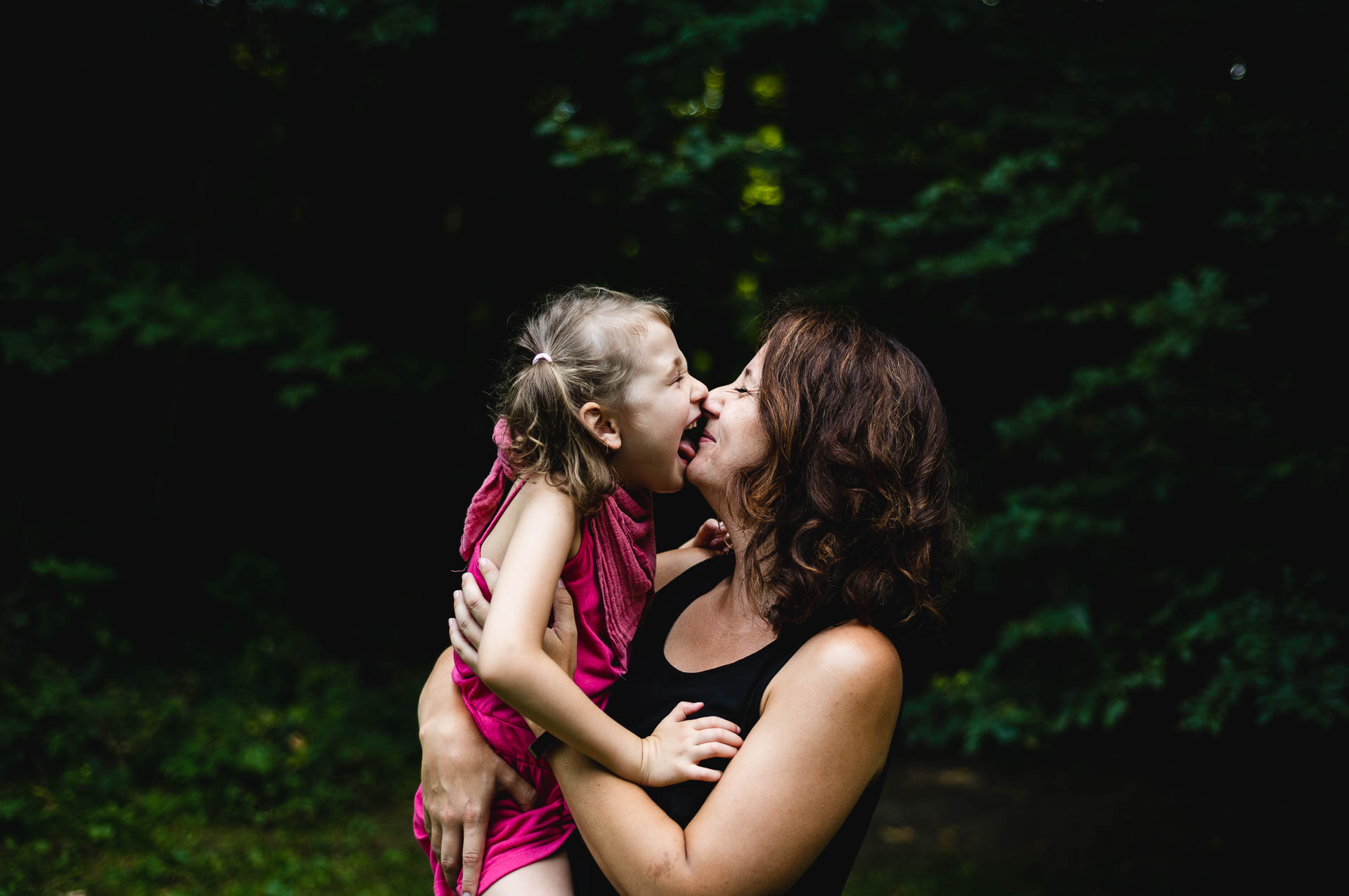 Mädchen in den Armen der Mutter gibt ihr ein Kuss auf der Nase