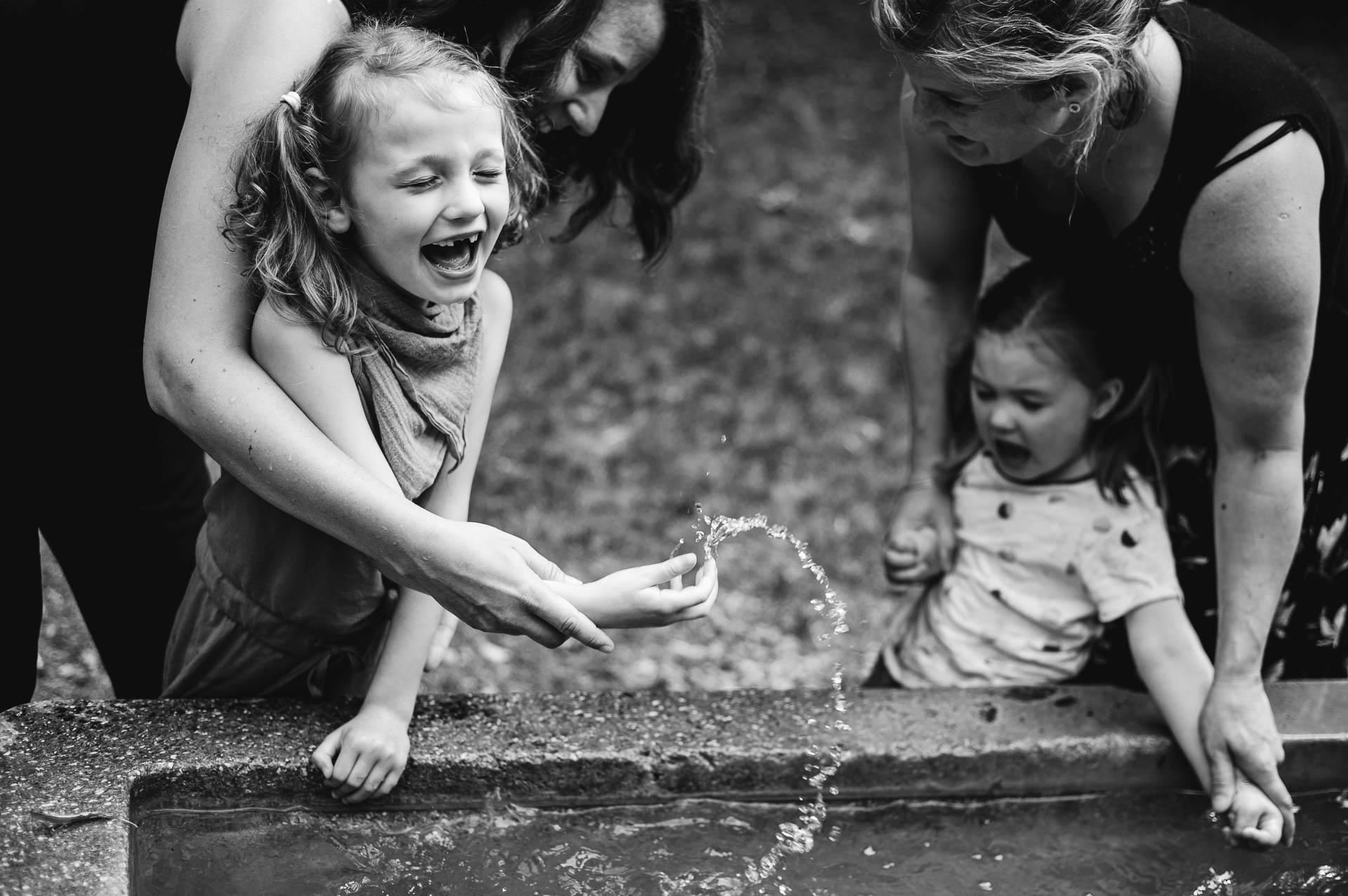 Zwei Mädchen mit Rett Syndrom und ihre Mütter spielen mit Wasser an einem Brunnen im Freien