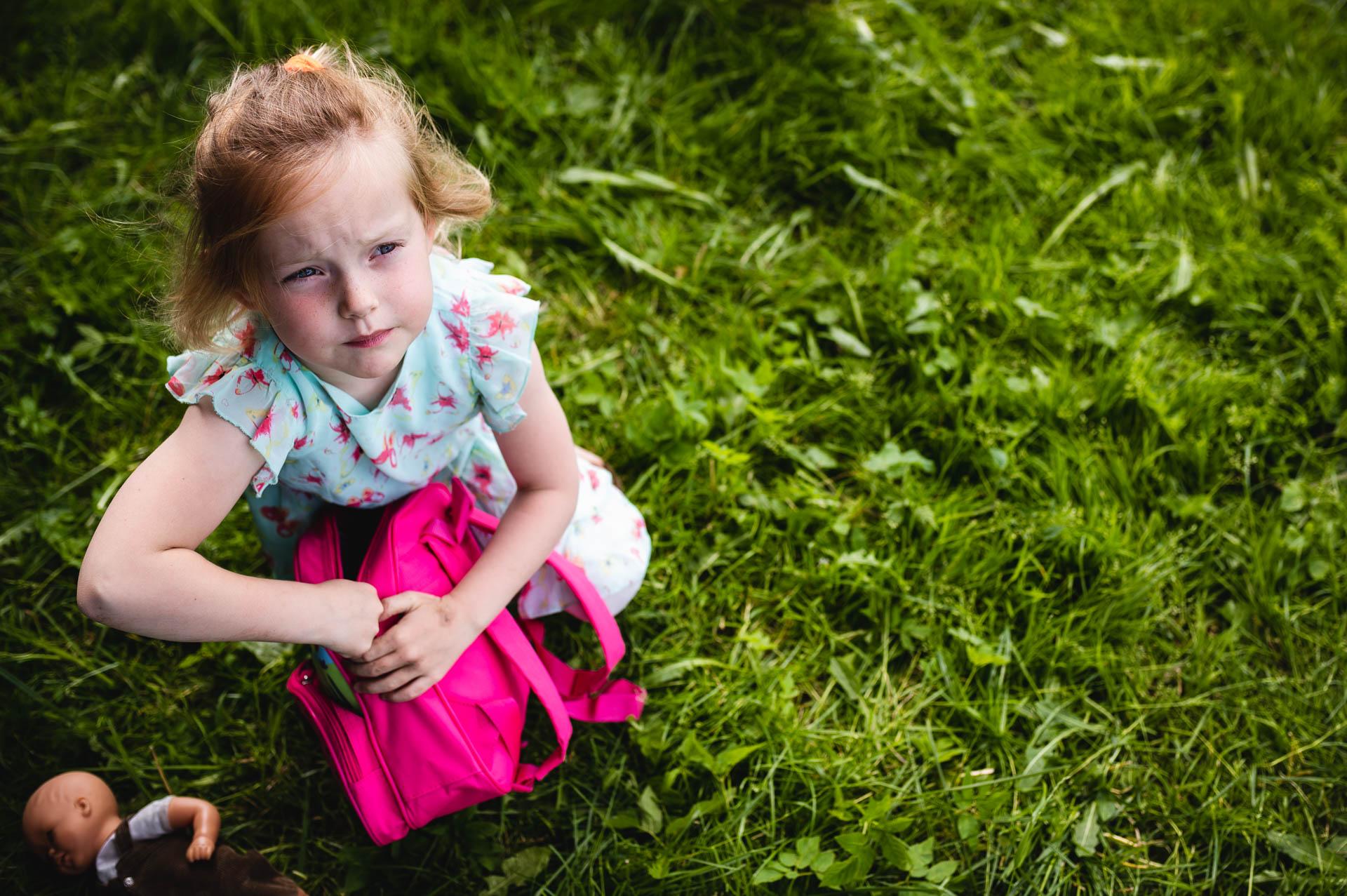 Mädchen im Sommerkleid auf der Wiese packt ihr pinkiges Rucksack, ihre Puppe liebt am Boden neben ihr