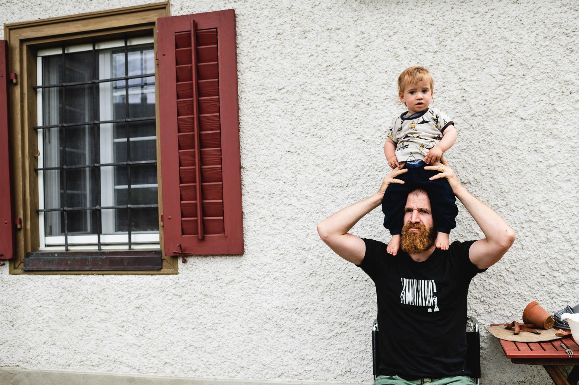 Kleinkind sitzt auf dem Kopf seines Vaters, der vor dem Haus sitzt