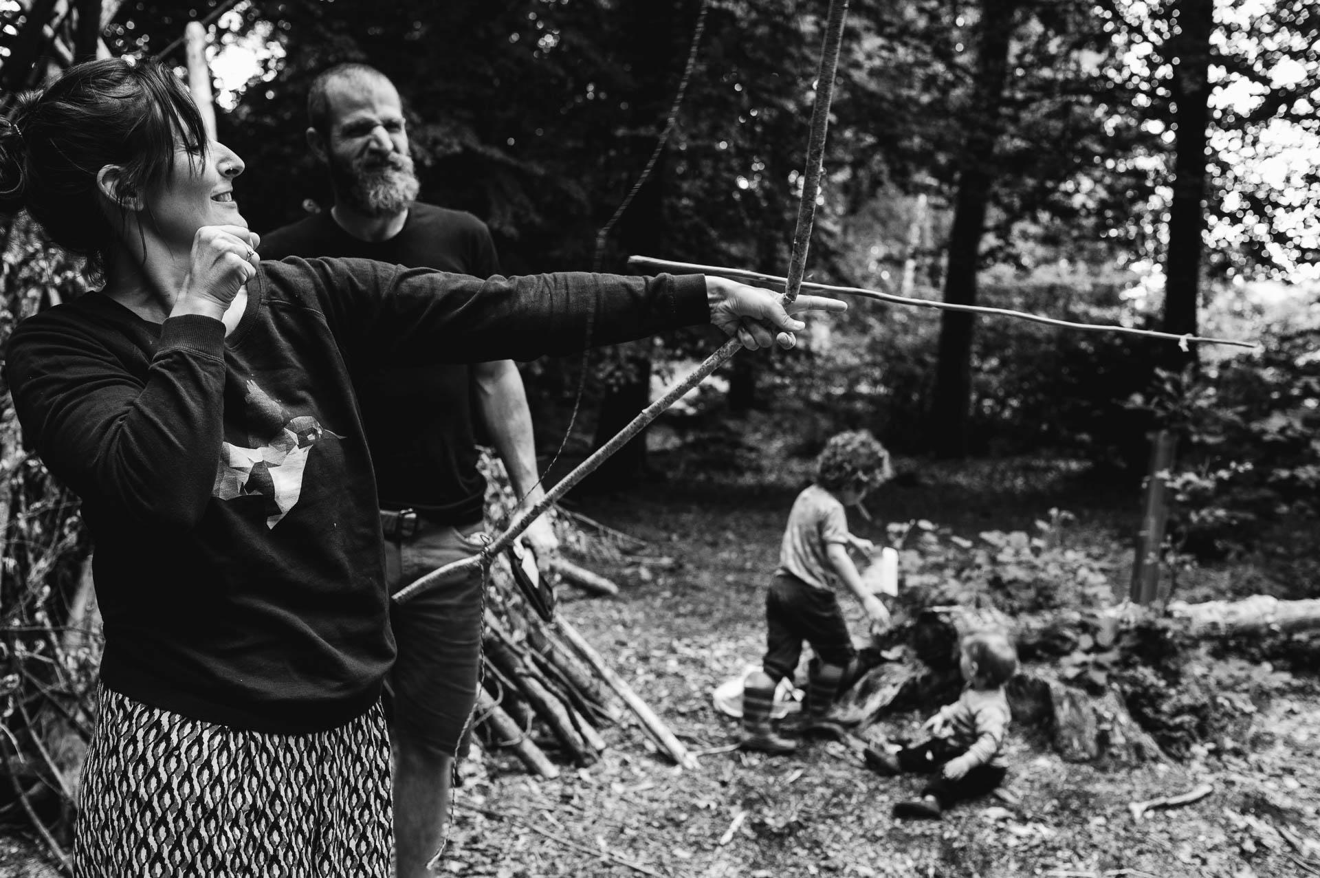 Frau wirft einen Ast mit Pfeilbogen im Wald und Mann schaut zu während die Kinder im Hintergrund spielen