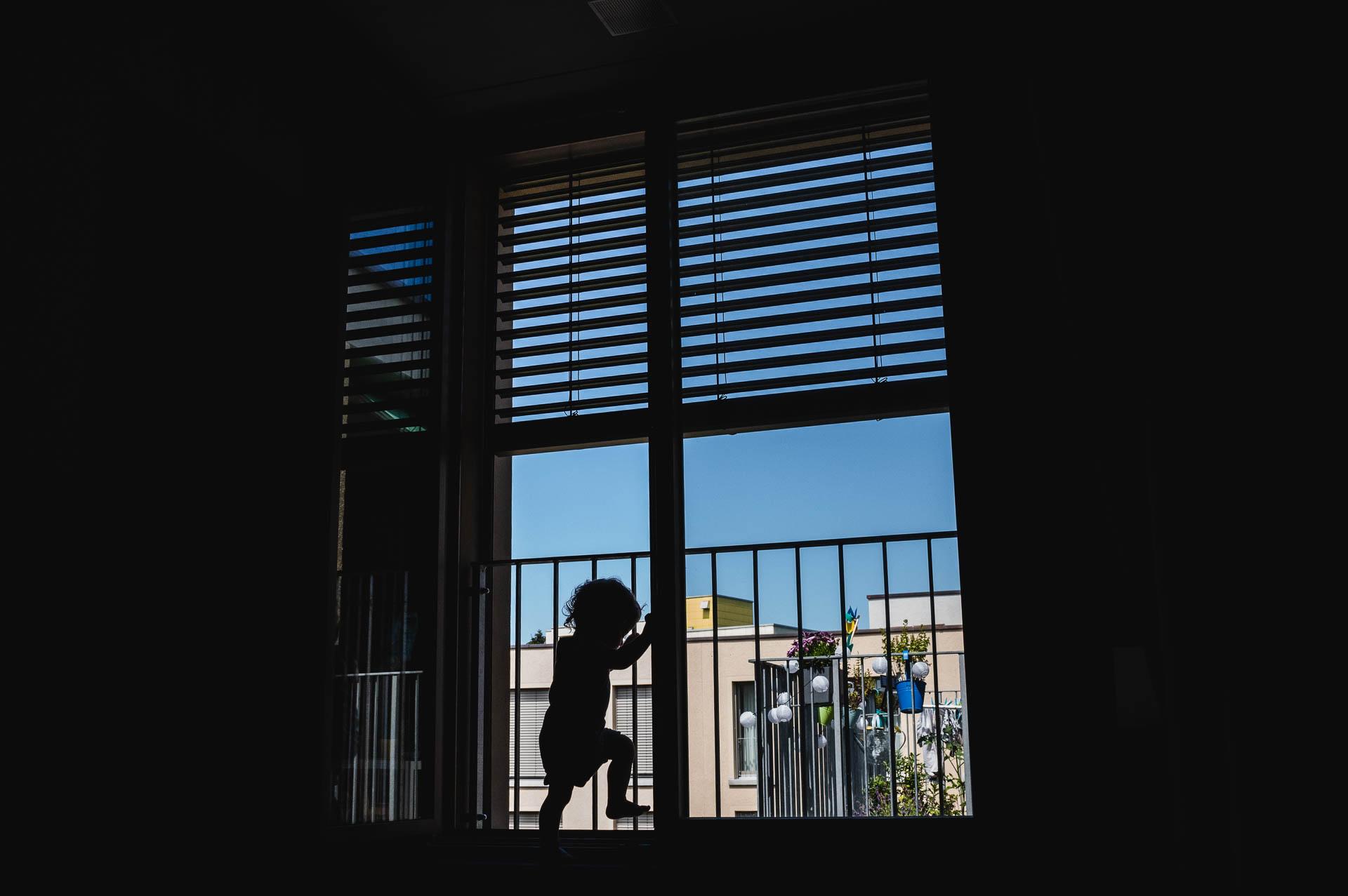 Silhouette eines Kleinkindes auf dem Balkonfenster mit Hochhaus im Hintergrund