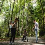 Mutter Vater und Kind im Wald diskutieren über den Weg, Kind ist auf dem Laufrad