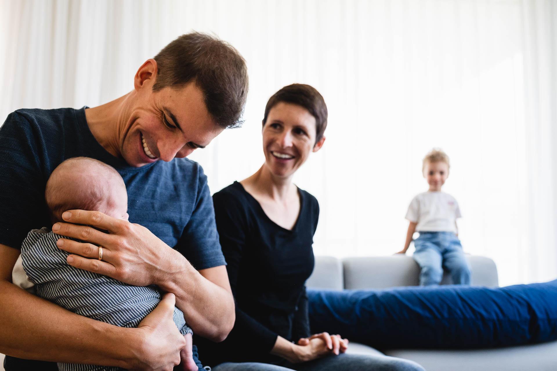 Vater hält sein kleines Baby und lächelt, die Mutter ist im Hintergrund und lächelt ebenfalls, die grössere Tochter sitzt auf der Sofalehne